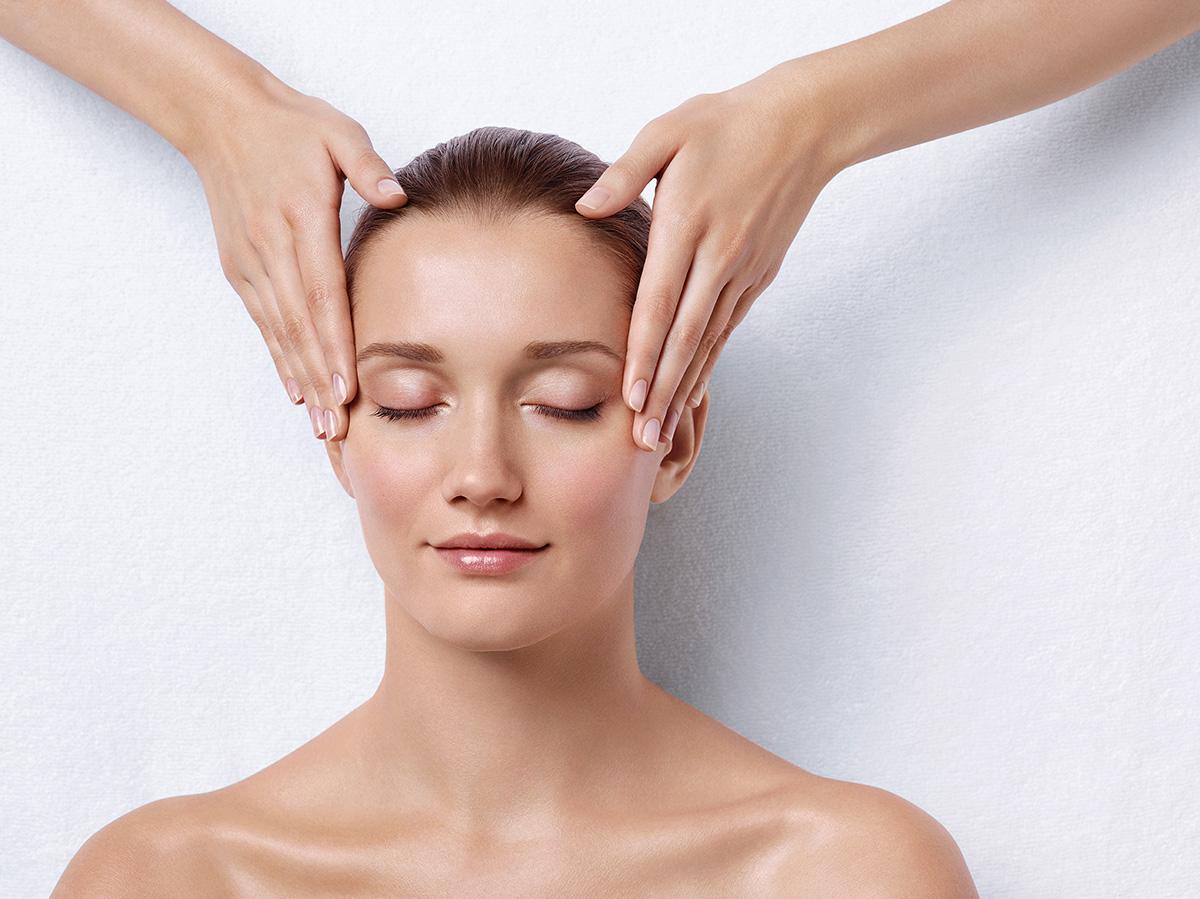 Mulher recebendo massagem na têmpora